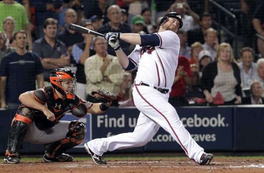 Braves catcher Brian McCann hits a sacrifice fly in the third inning to score Omar Infante. Photo: Dave Martin, AP