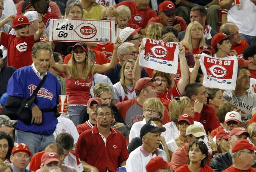Reds fans try to rally their team in the sixth inning.