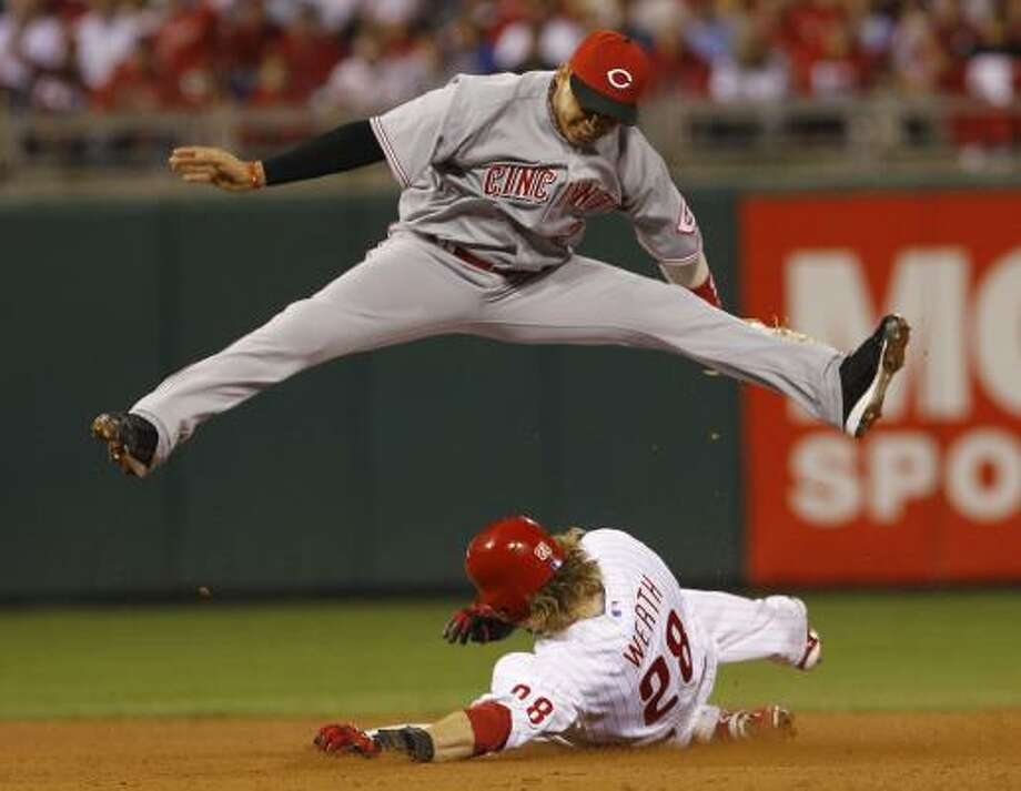 Reds shortstop Orlando Cabrera jumps over Philadelphia's Jayson Werth after forcing him out at second base and turning a double play during the fourth inning. Photo: Mel Evans, AP