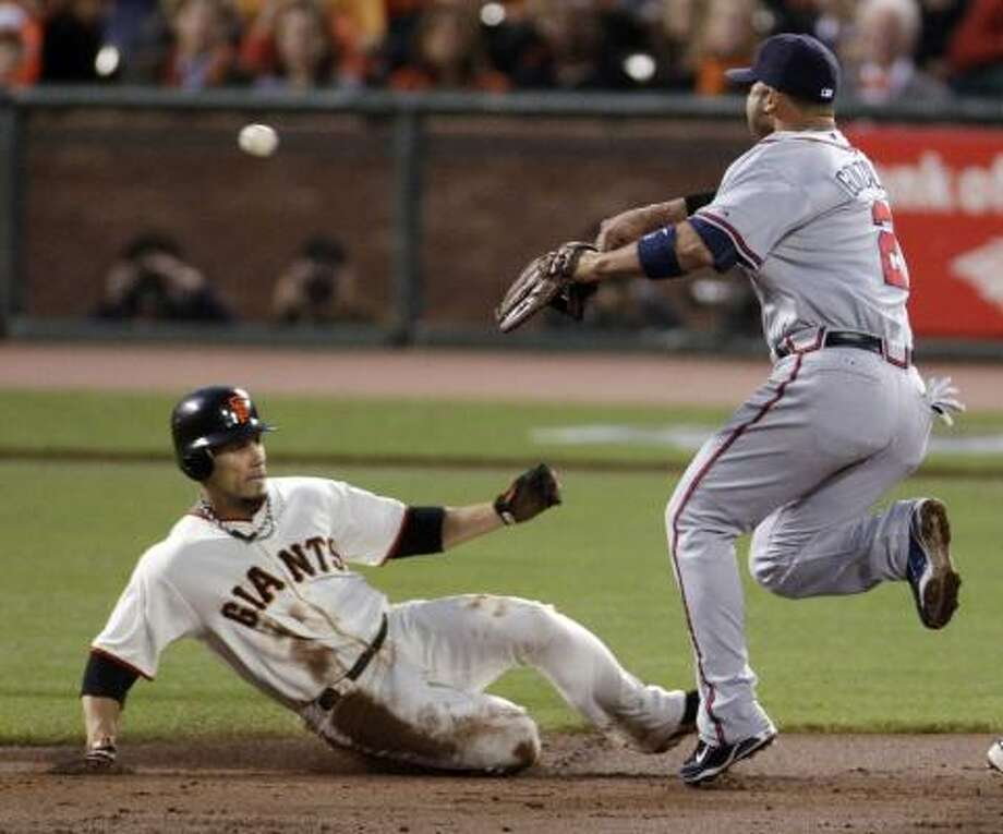 Braves shortstop Alex Gonzalez throws to first base to complete a double play after forcing out San Francisco's Freddy Sanchez, left, during the first inning. Photo: Jeff Chiu, AP