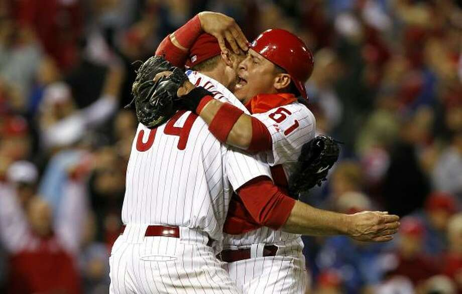 Roy Halladay, left, celebrates with catcher Carlos Ruiz after tossing a no-hitter in Game 1 against the Reds. Photo: Jeff Zelevansky, Getty Images