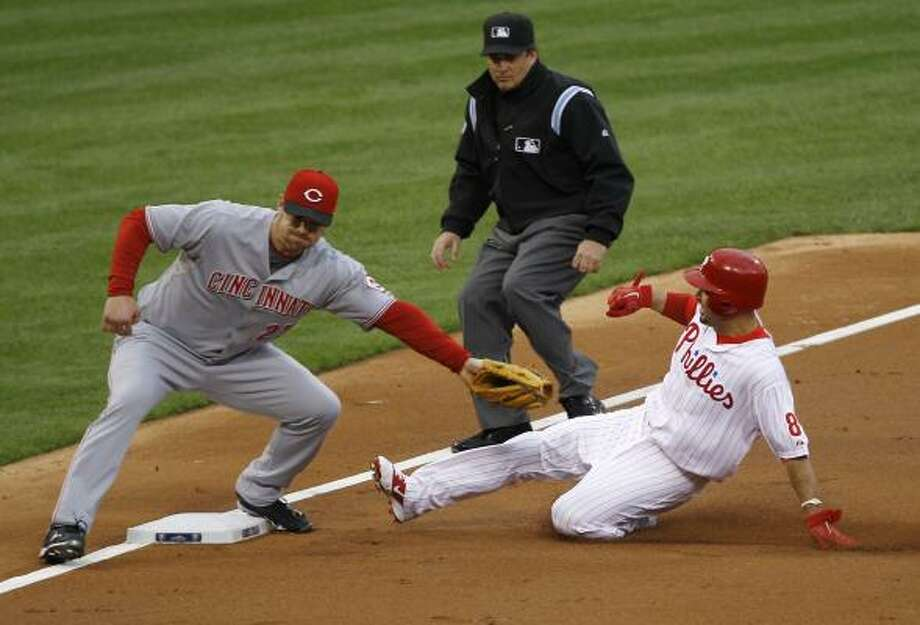 Philadelphia's Shane Victorino steals third base as Reds third baseman Scott Rolen applies the late tag during the second inning. Photo: Matt Rourke, AP