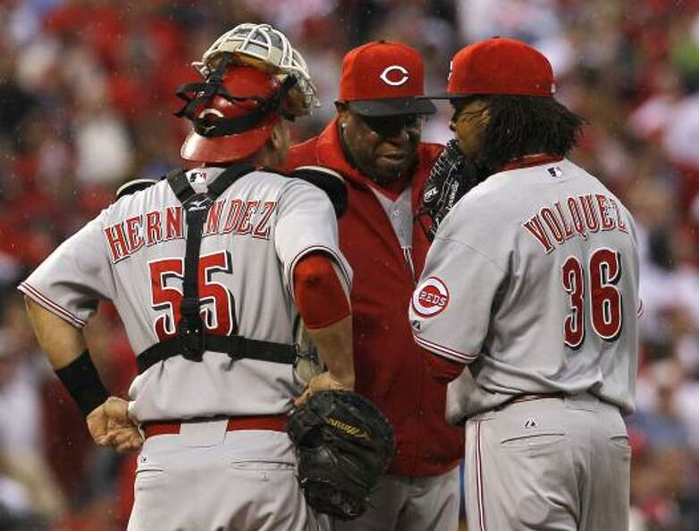Reds manager Dusty Baker, center, talks with catcher Ramon Hernandez (55) and starting pitcher Edins
