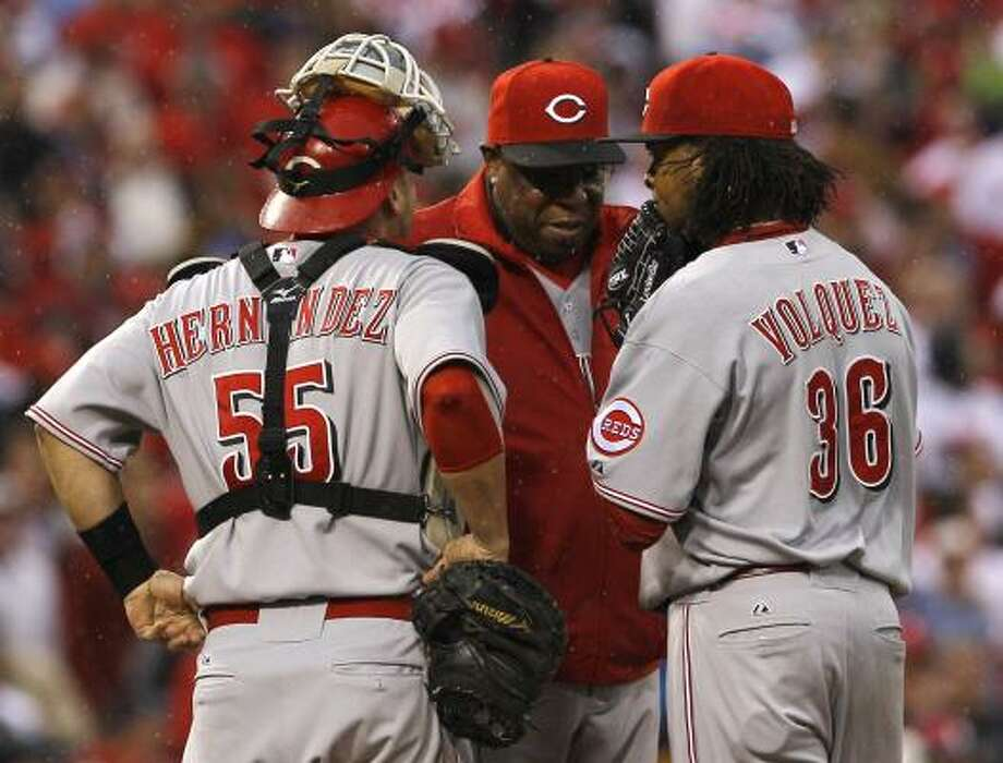 Reds manager Dusty Baker, center, talks with catcher Ramon Hernandez (55) and starting pitcher Edinson Volquez before pulling Volquez in the second inning. Photo: Mel Evans, AP