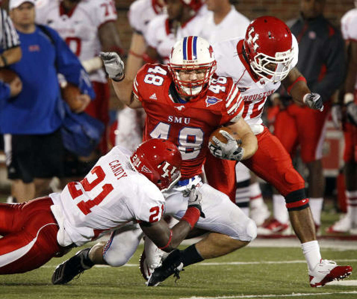 SMU running back Zach Line (48) is brought down by UH safety Jacky Candy (21) and cornerback Jamal Robinson (32) during the third quarter.