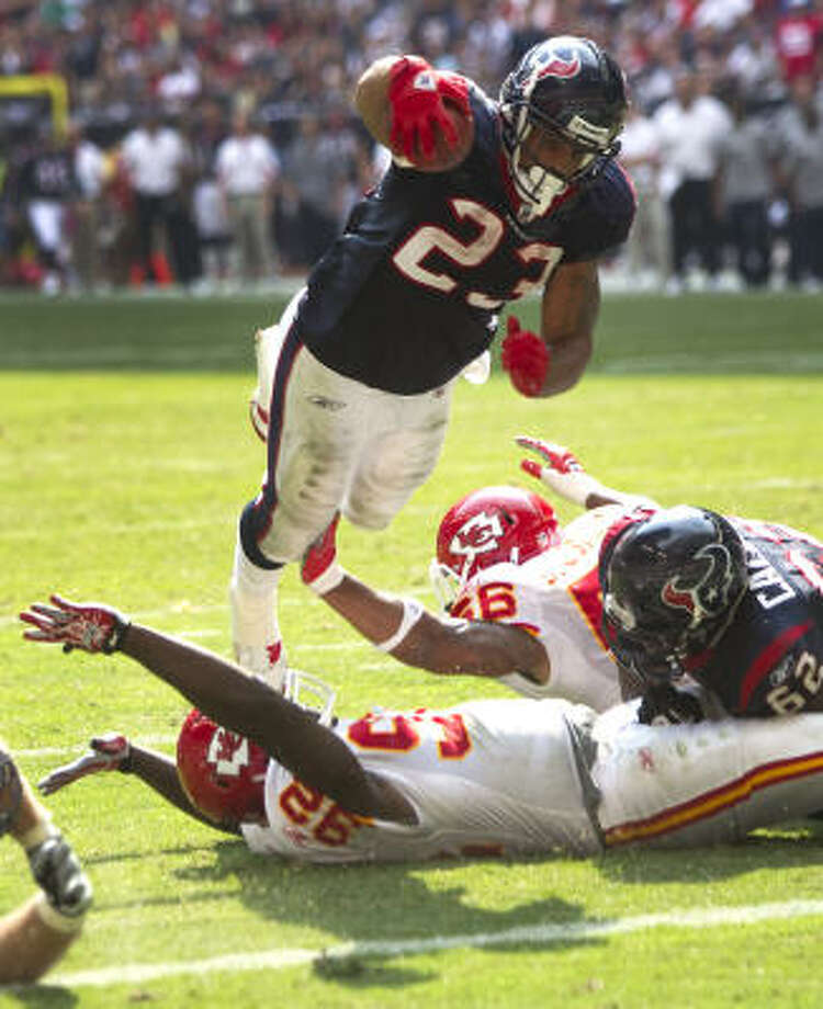 Texans running back Arian Foster dives over Chiefs defensive end Wallace Gilberry for a 1-yard touchdown. Photo: Brett Coomer, Chronicle