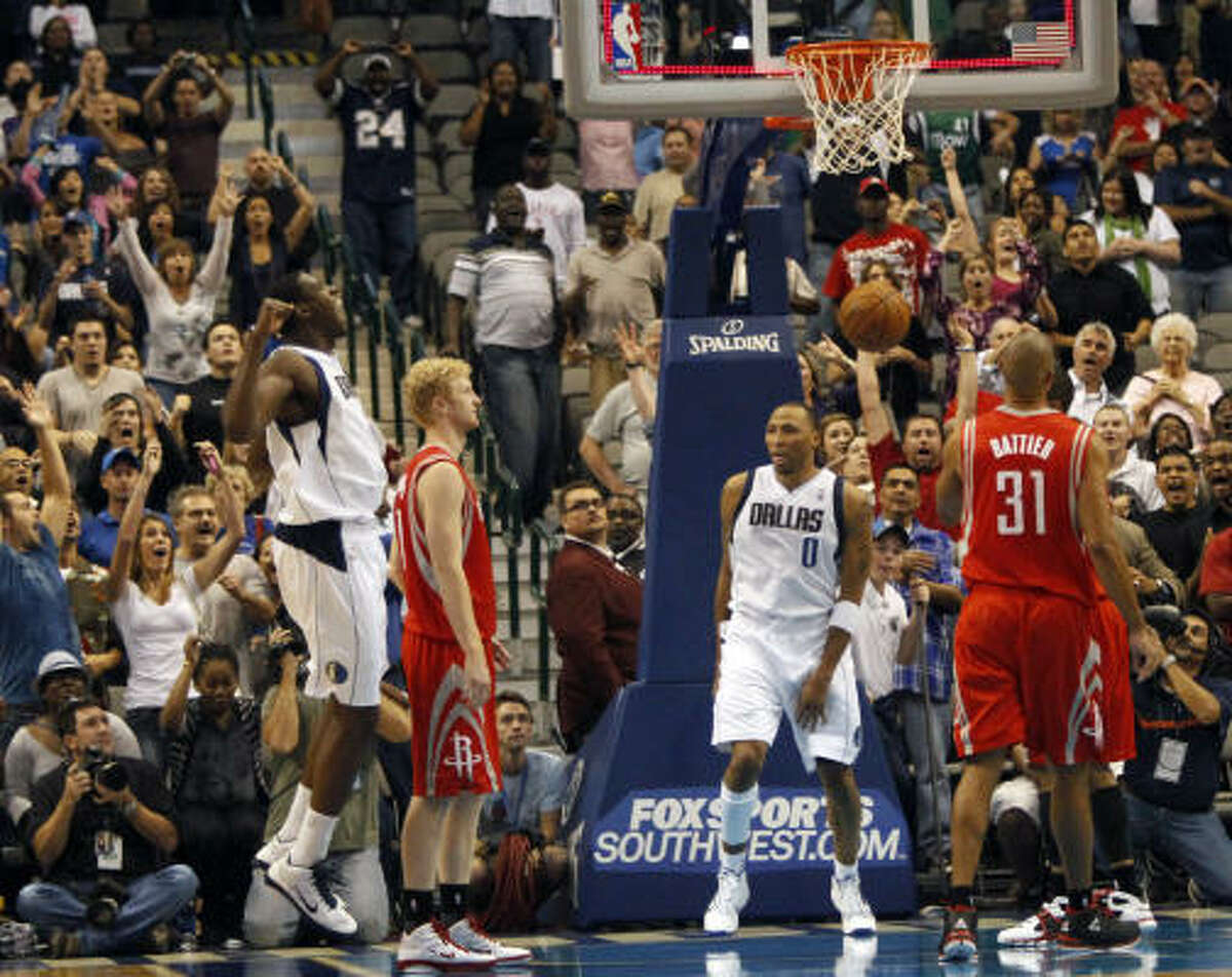 Mavericks forward Shawn Marion (0) and center Ian Mahinmi, left, celebrate a last-second win as Rockets forward Chase Budinger, left, and forward Shane Battier (31) watch.