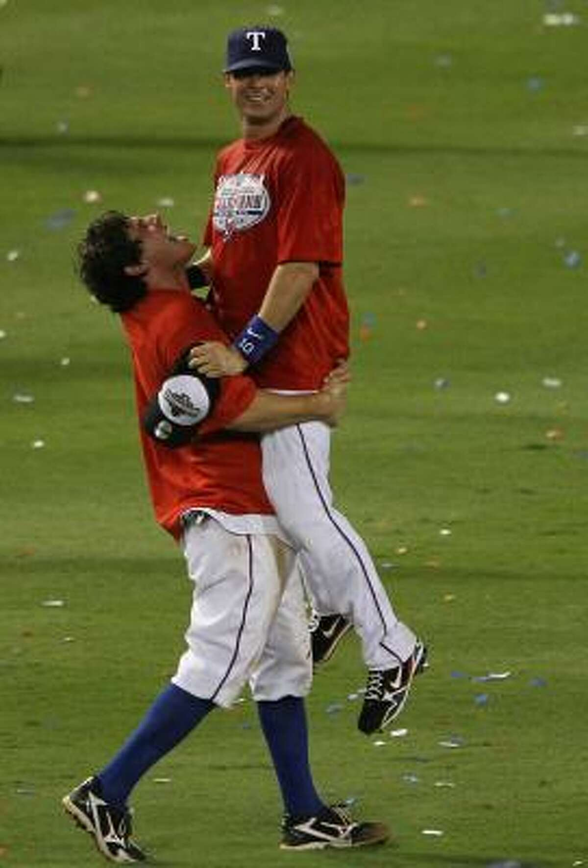 Ian Kinsler of the Texas Rangers picks up teammate Michael Young as they celebrate on the field after defeating the New York Yankees.