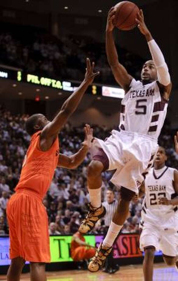 Texas A&M's Dash Harris (5) drives against Oklahoma State's Reger Dowell in A&M's 76-61 victory. Photo: Dave Einsel, AP