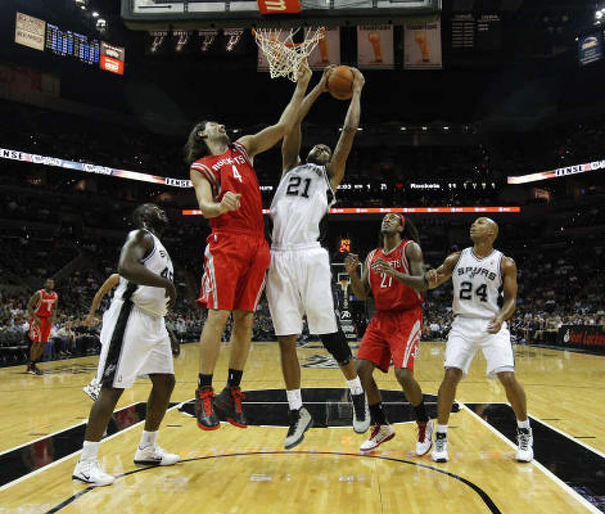 Spurs forward Tim Duncan pulls down a rebound in front of Rockets forward Luis Scola.