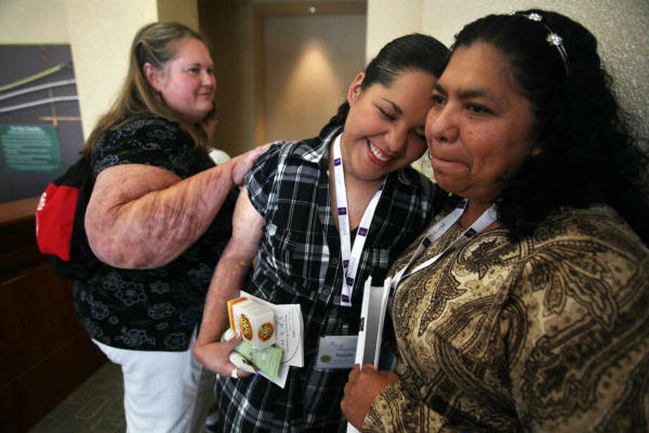 Michelle Reynolds, 38, of Hartville, Ohio, greets fellow burn survivor Rosalba Alvarez, of Mexico City, and Alvarez's mother, Rosalba Guyton. The World Burn Congress drew 800 registered burn survivors. Photo: Mayra Beltran, Chronicle