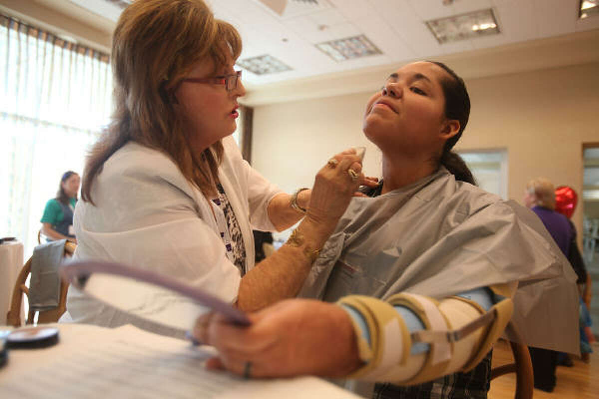 Cosmetologist Deb Kellert, of Canada, applies makeup to Alvarez.