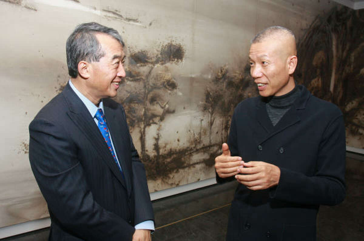 Albert Y. Chao, left, with artist Cai Guo-Qiang in front of Cai's gunpowder drawing Odyssey at the Museum of Fine Arts, Houston patrons dinner celebrating the opening of the Ting Tsung and Wei Fong Chao Arts of China Gallery.