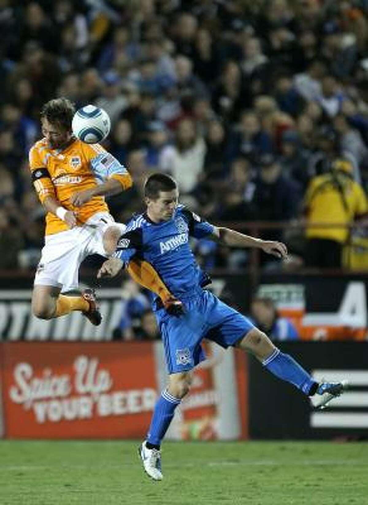 Dynamo midfielder Brad Davis, left, and San Jose's Sam Cronin go up for the ball.