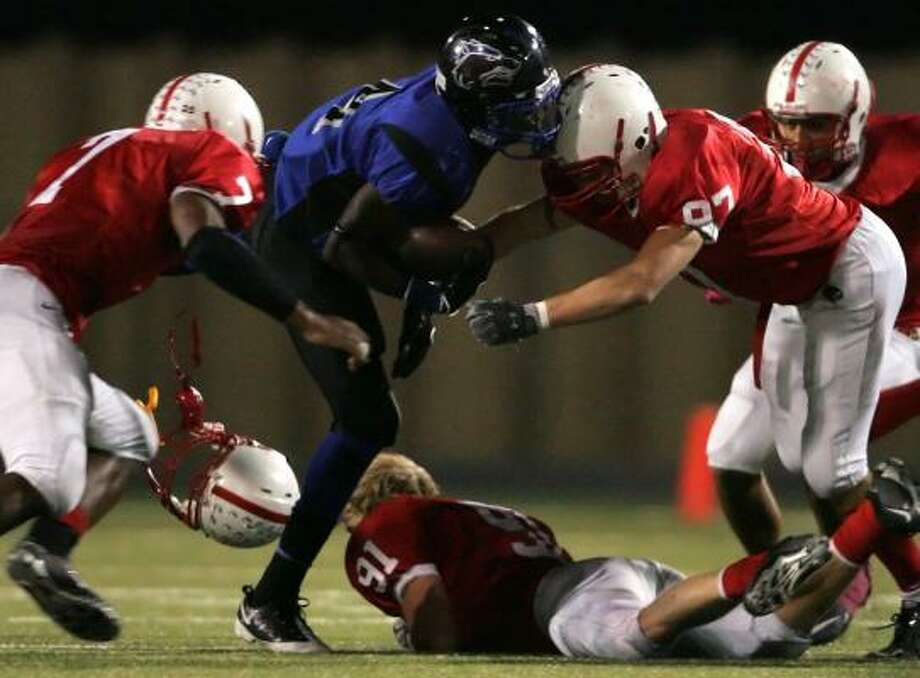 Oct. 16: Bellaire 28, Chavez 27Chavez's Derrick Coleman (4) is tackled by Bellaire's Keith Ewing (7) and Collin Speich (97) as teammate Michael Holland loses his helmet in the fourth quarter at Butler Stadium. Photo: ERIC CHRISTIAN SMITH, FOR THE CHRONICLE