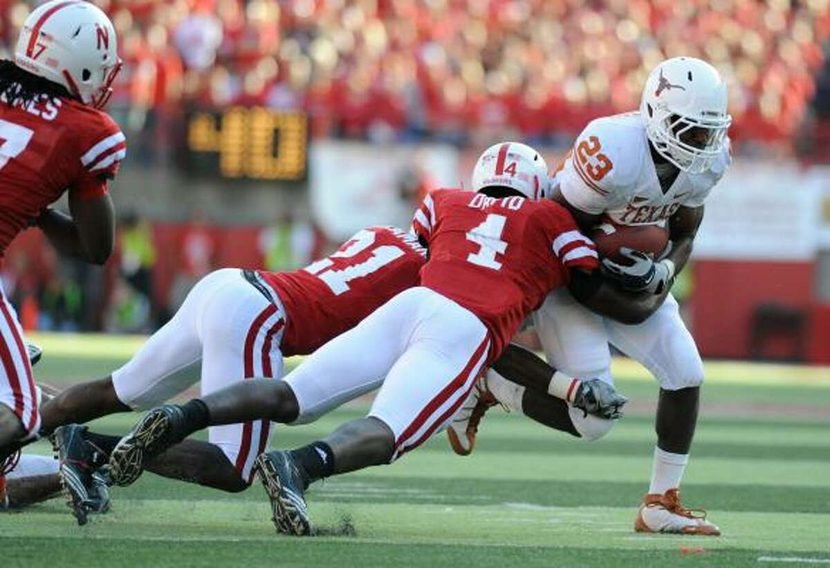 Texas running back Tre' Newton (23) gets wrapped up by Nebraska linebacker Lavonte David (4) and cornerback Prince Amukamara during the second half.