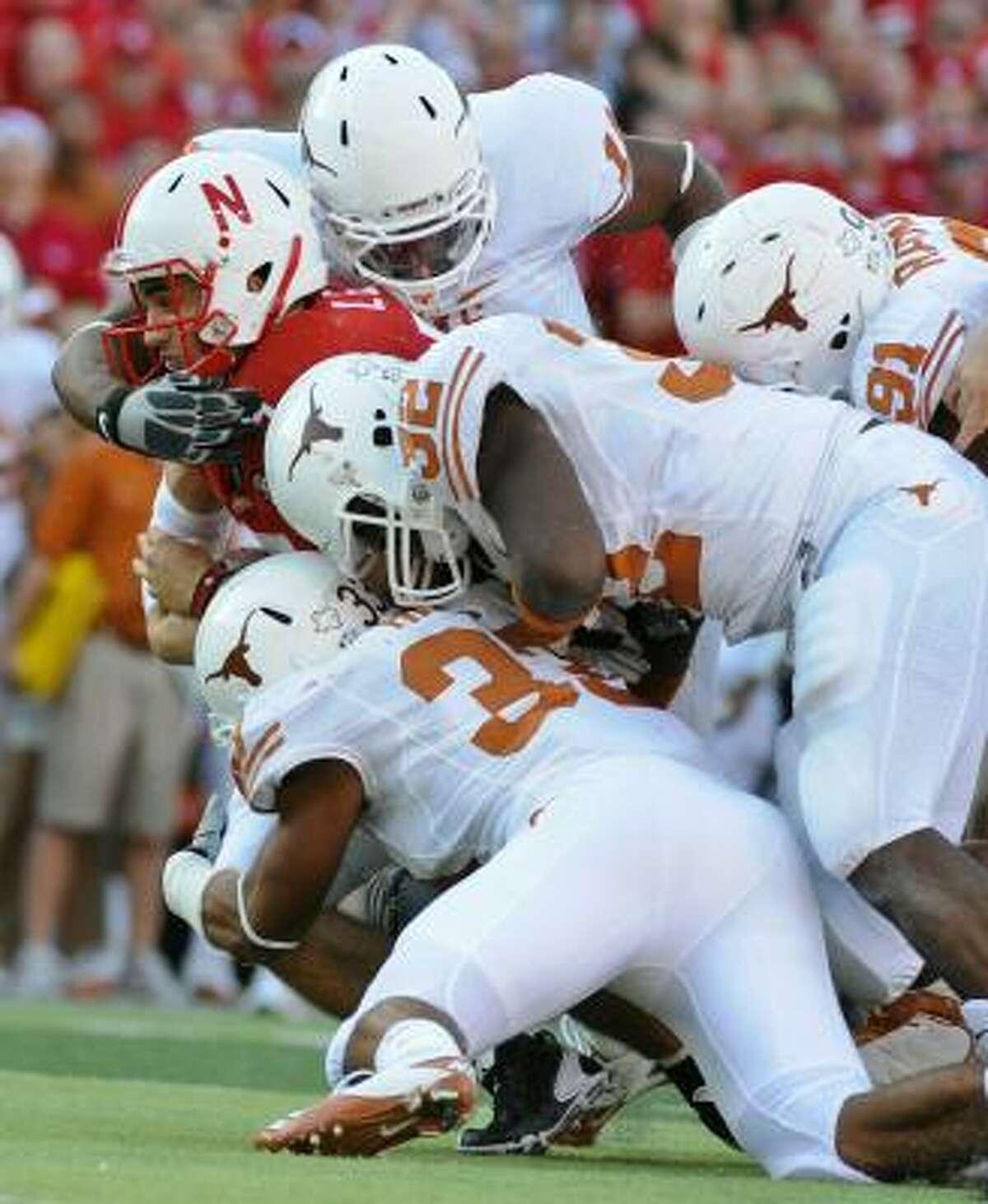 Nebraska quarterback Zac Lee is tackled by a host of Texas defenders.
