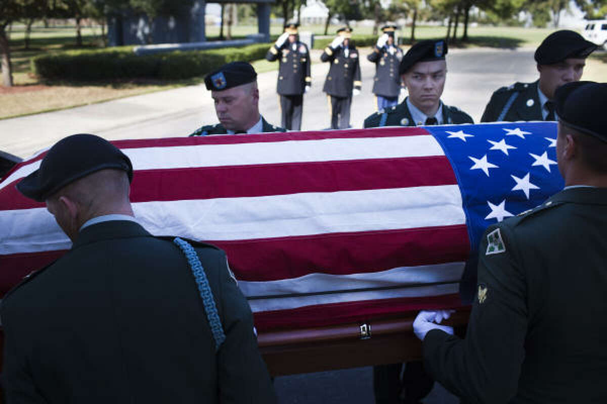 Soldiers transfer the casket of David H. McNerney from a hearse to a caisson at the Houston National Cemetery.