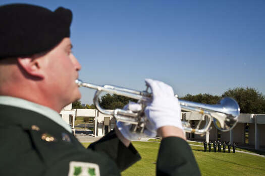 Taps are played during the service of David H. McNerney at the Houston National Cemetery as a rifle volley team stands in the background. Photo: Eric Kayne, For The Chronicle