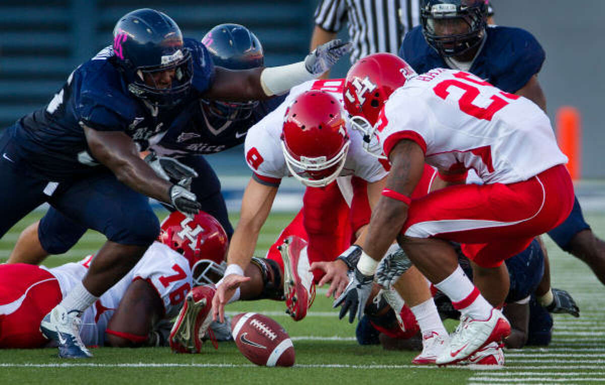 Oct. 16: Rice 34, UH 31 UH quarterback David Piland (8) and running back Michael Hayes (29) chase a fumble lost by Piland as Rice defensive end Cheta Ozougwu, left, closes in during the fourth quarter. Piland fumbled the snap on fourth-and-inches from the Rice 37 with 1:37 left in the game, allowing the Owls to sneak away with a victory.