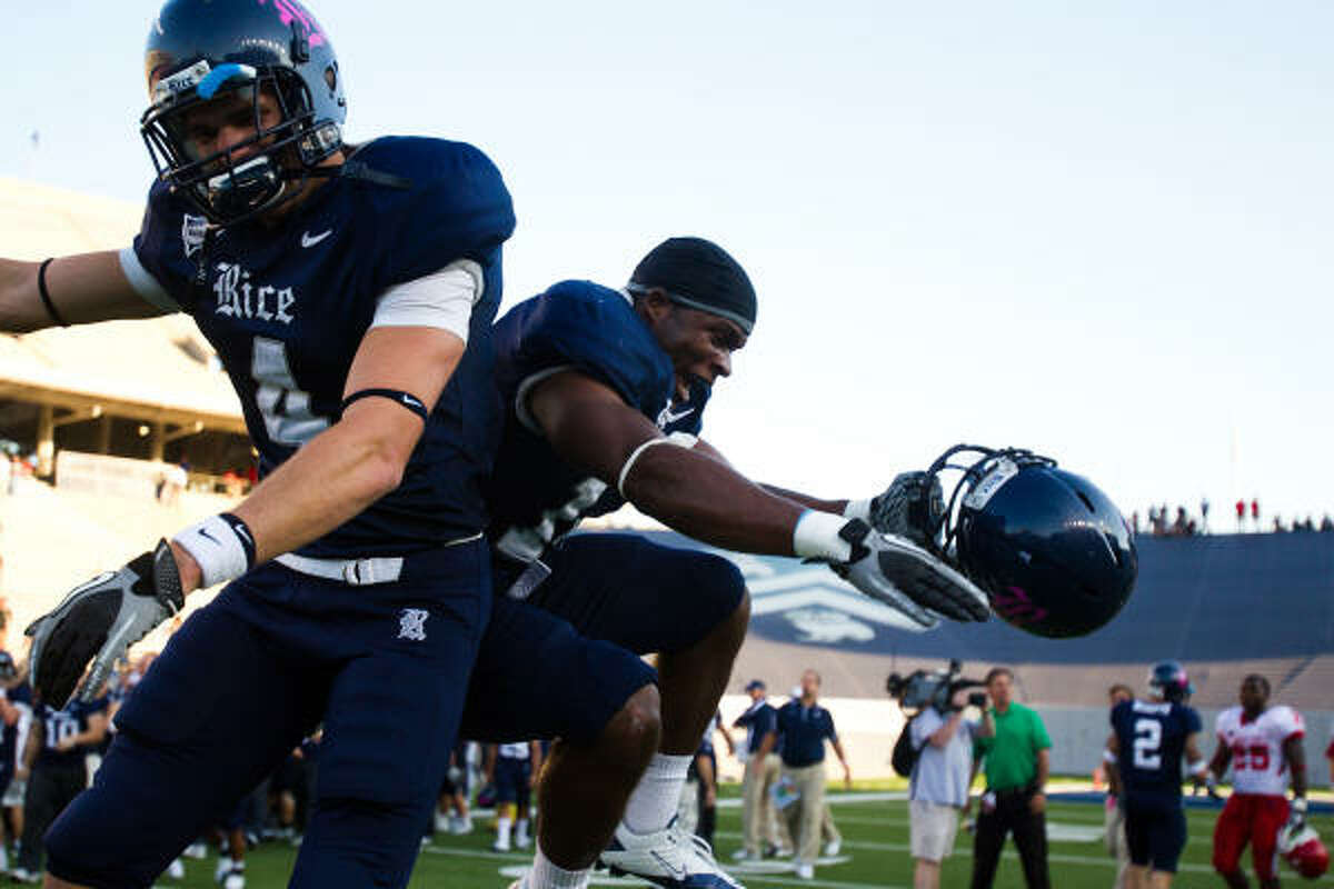 Owls wide receiver Randy Kitchens (4) and safety Xavier Webb celebrate after defeating the Cougars.