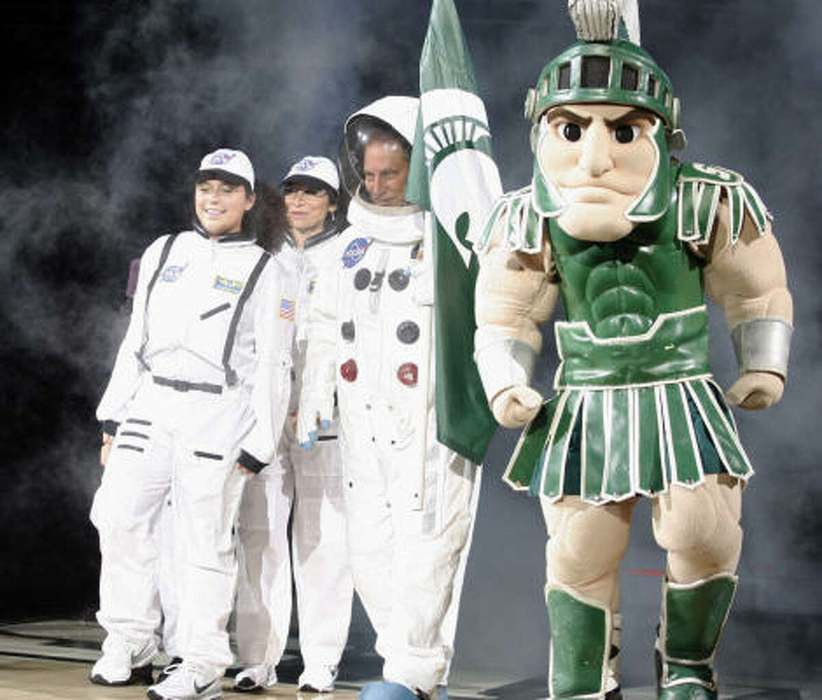 Michigan State coach Tom Izzo, center, arrives with daughter Racquel, left, wife Lupe, and mascot Sparty, right.