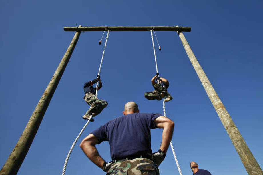 Shawn Casey watches as his fellow Plano S.W.A.T. members, Jeff Kranz and Steve Young climb ropes during the obstacle course of the Texas Tactical Police Officers Association (TTPOA) annual state S.W.A.T. competition at the Harris County Sheriff's Office Academy in Houston.  The Plano team went on to place second in the overall standings of the TTPOA S.W.A.T. competition.  The HCSO hosted the 4-day event, which kicked off on Monday, Oct. 11 with more than a dozen teams from across Texas compete in events such as sniper, hostage rescue, and night operations. The competition encourages high standards of physical fitness and tactical training for tactical officers and teams. Photo: Michael Paulsen, Chronicle