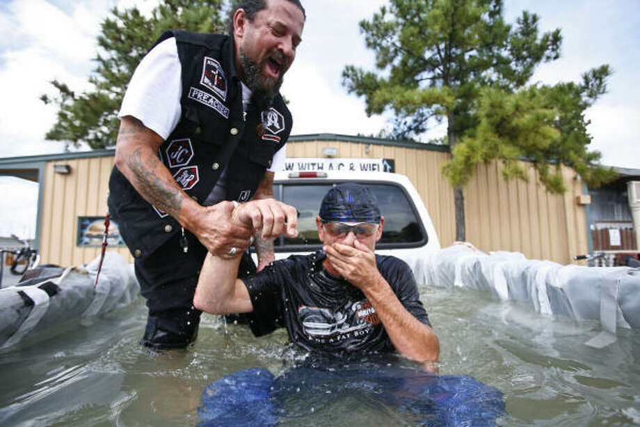 The Rev. David Loa baptizes Bill Carroll in the back of a pickup truck parked at the County Line Bar and Grill  in Richmond. Photo: Michael Paulsen, Chronicle