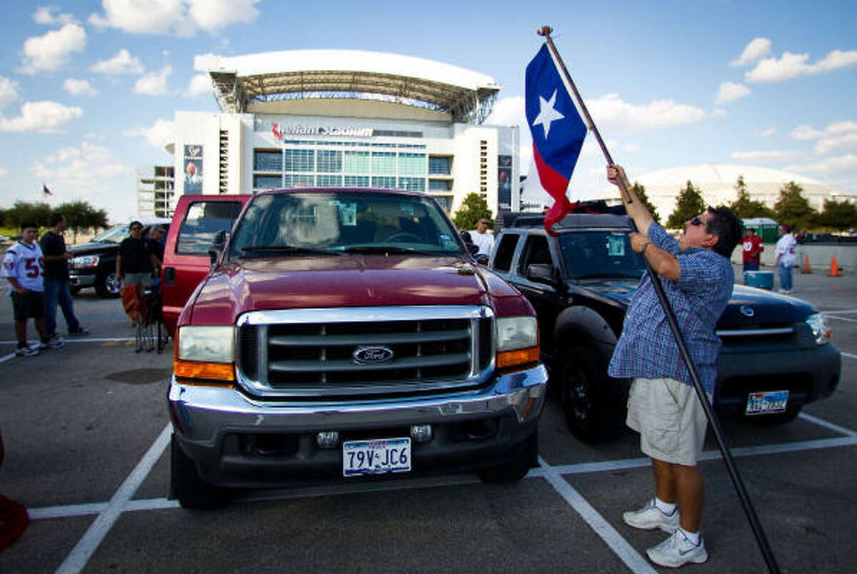 David Palomo of Houston, takes down his flags as he and his family clean up after attending the Texan's game against the Giants. Palomo, a season ticket holder for three years, says the new rules about tailgaters will not affect him. Palomo also says that last home games problems give Texans fans a black eye saying that it's the first time he's ever known about a situation.