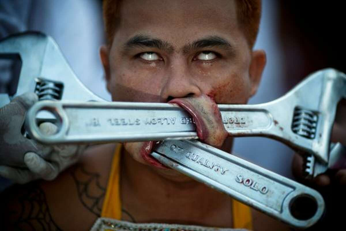 A devotee of the Chinese shrine of Samkong pierces his cheeks with wrenchs during the Vegetarian Festival in Phuket, Thailand.