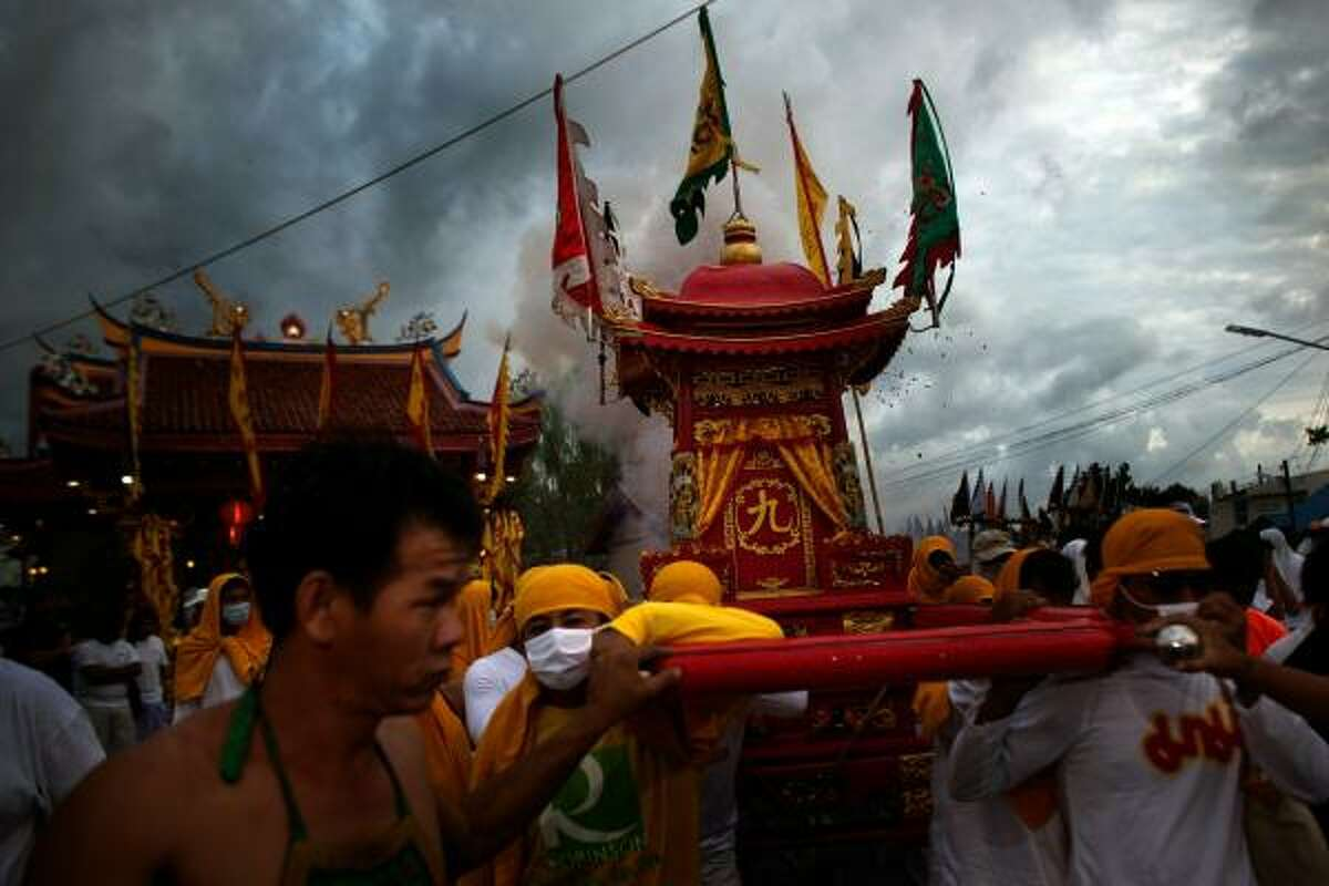 Devotees carry a Chinese god on a palanquin as firecreckers explode during a procession. Ritual Vegetarianism in Phuket Island traces it roots back to the early 1800s.