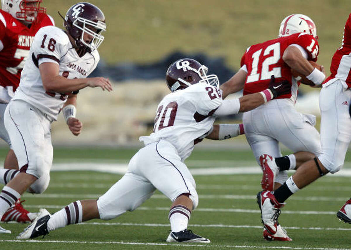 Memorial quarterback Wayne Taylor (12) is tackled from behind by Cinco Ranch's Taylor Holt.