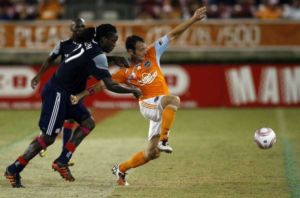 Dynamo midfielder Brad Davis, right, fends off New England's Shalrie Joseph during the first half of Sunday's match at Robertson Stadium. The Dynamo lost 2-1.