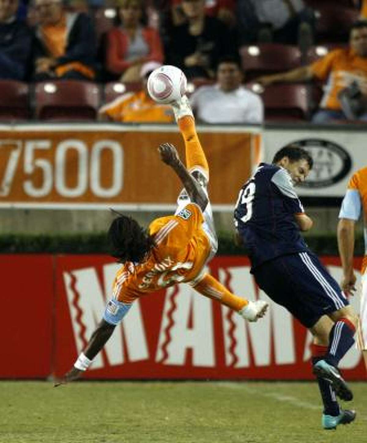 The Dynamo's Adrian Serioux clears as the Revolution's Marko Perovic cringes.