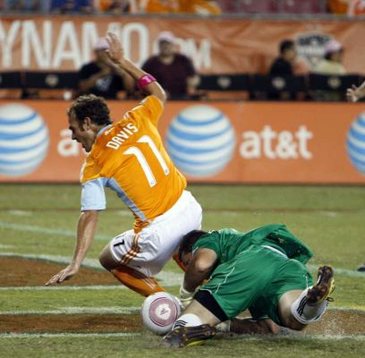 Dynamo midfielder Brad Davis (11) collides with Revolution goalkeeper Bobby Shuttleworth while attempting to score in the first half.