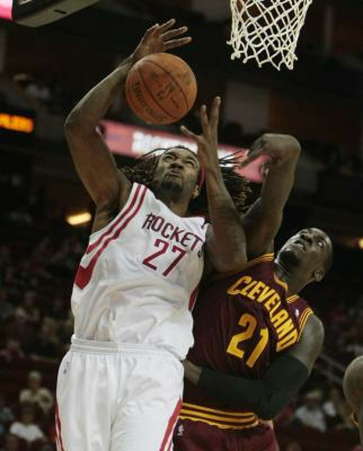 Rockets center Jordan Hill has the ball knocked from his hands on an offensive rebound by Cavaliers forward J.J. Hickson.