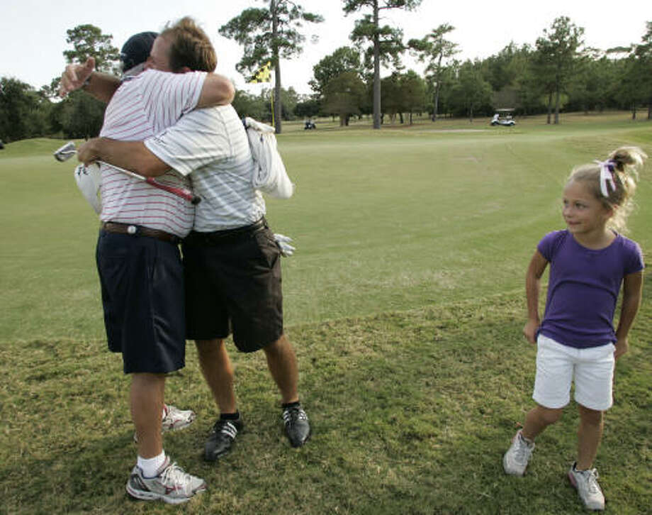 Greater Houston City Amateur champion Kip Guidry, second from left, hugs his father Kirby as Guidry's daughter Danni, 9, looks on after Guidry's one-shot victory over Justin Kaplan. Photo: ERIC CHRISTIAN SMITH, For The Chronicle
