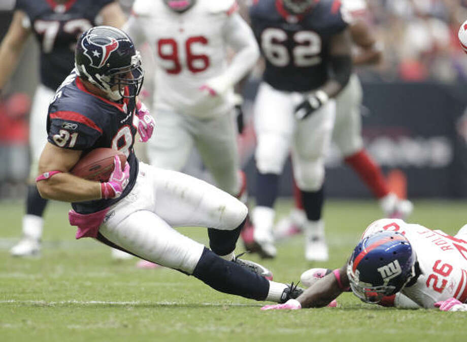 Texans tight end Owen Daniels is tripped up by Giants safety Antrel Rolle on a play in the second quarter of Sunday's game at Reliant Stadium. The Texans lost 34-10. Photo: Karen Warren, Chronicle