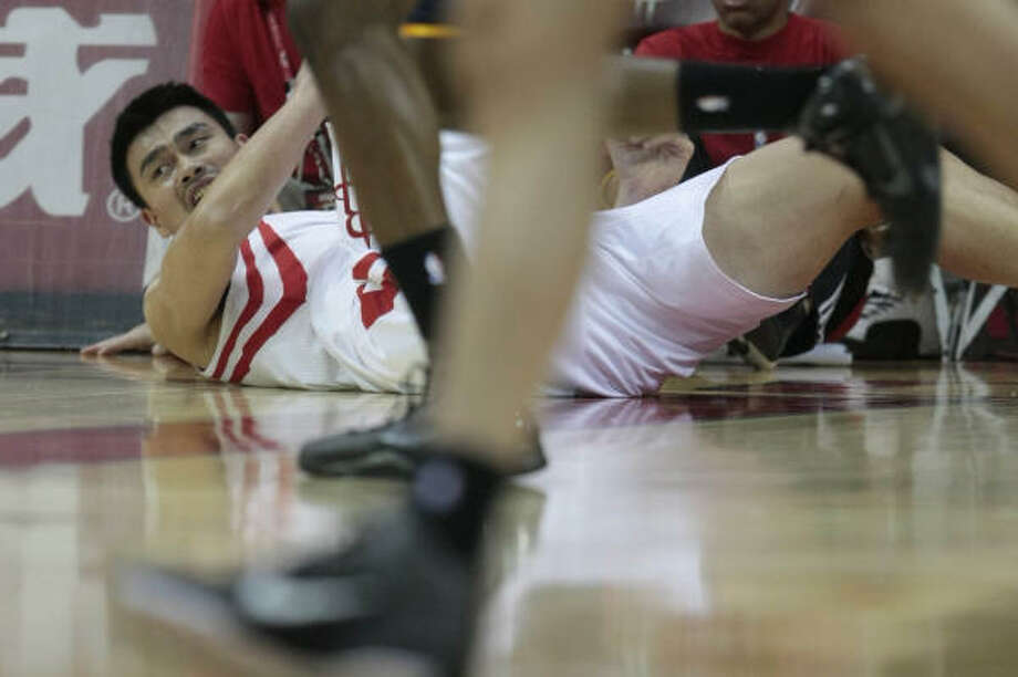 Rockets center Yao Ming looks down the court after falling while fighting for a loose ball. Photo: Billy Smith II, Chronicle