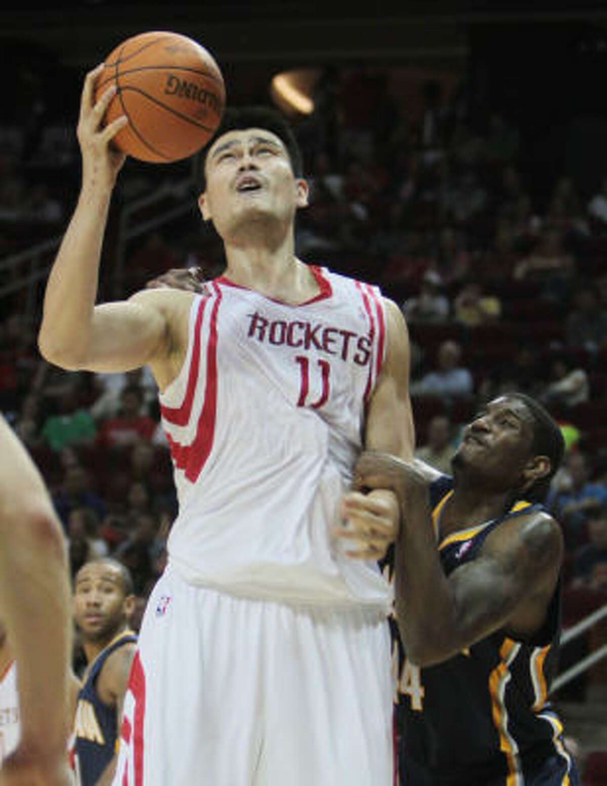 Rockets center Yao Ming attempts a shot while being pulled and held by Pacers forward Solomon Jones.