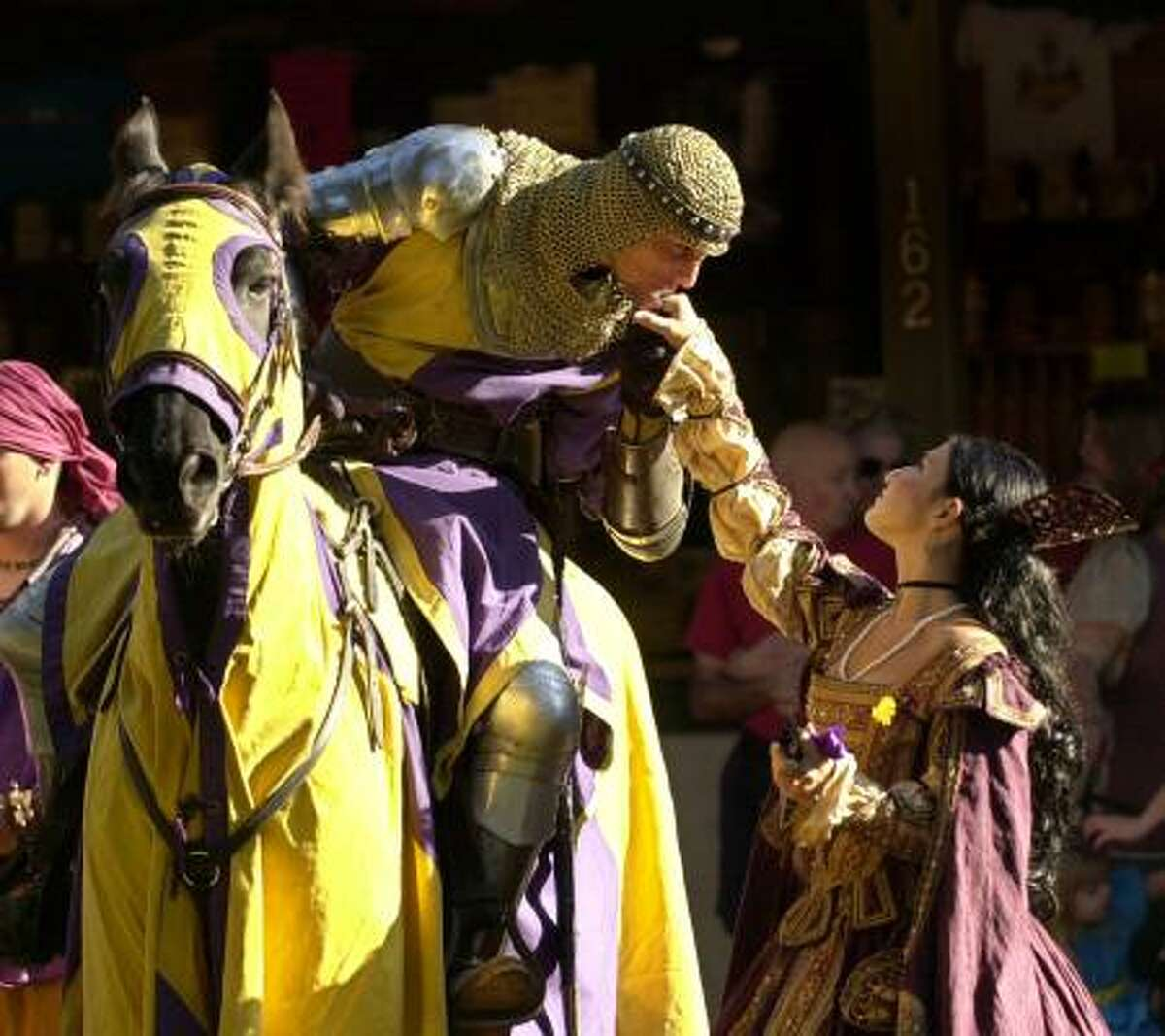 Knight Don Rodrigo Duke of Santiago, played by Chris Mitri Dynneson, kisses the hand of Dona de Salamanco, played by Sylvia Salamanca during the opening ceremony at the Texas Renaissance Festival in 2003.