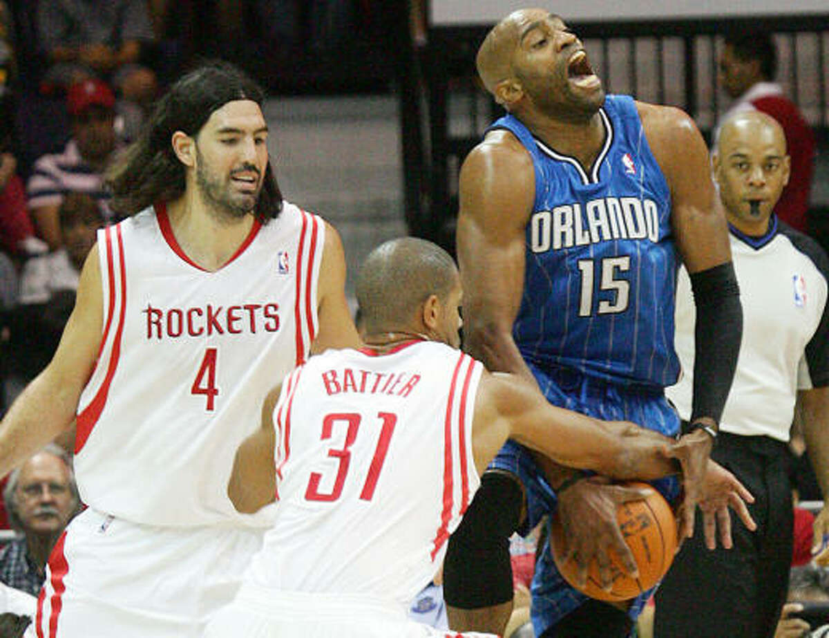 Rockets forwards Luis Scola (4) and Shane Battier defend Orlando Magic guard Vince Carter during the first half.