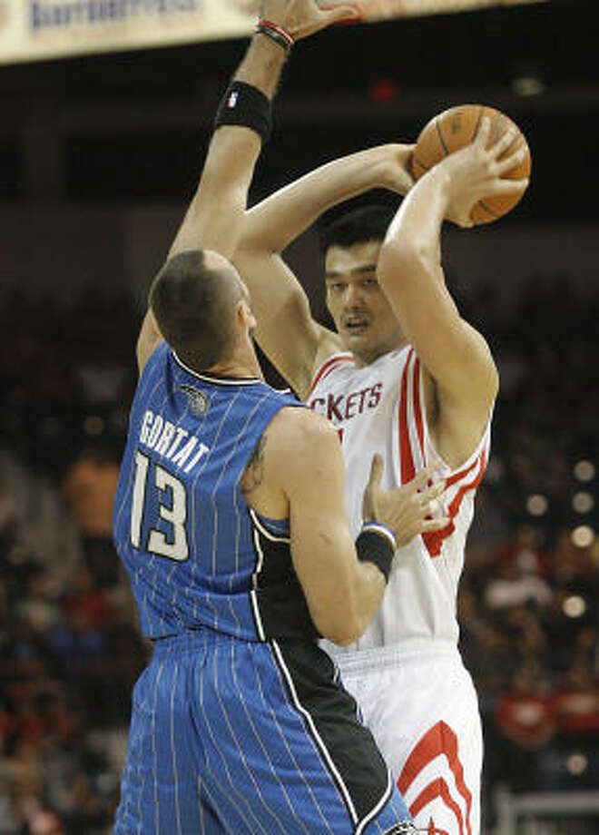 Rockets center Yao Ming is defended by Magic center Marcin Gortat during the first quarter. Photo: Delcia Lopez, AP