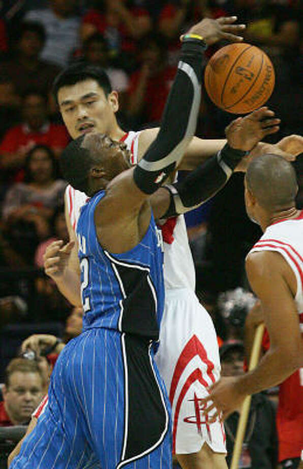 Magic center Dwight Howard drives on Rockets center Yao Ming, rear, during the first quarter. Photo: Delcia Lopez, AP
