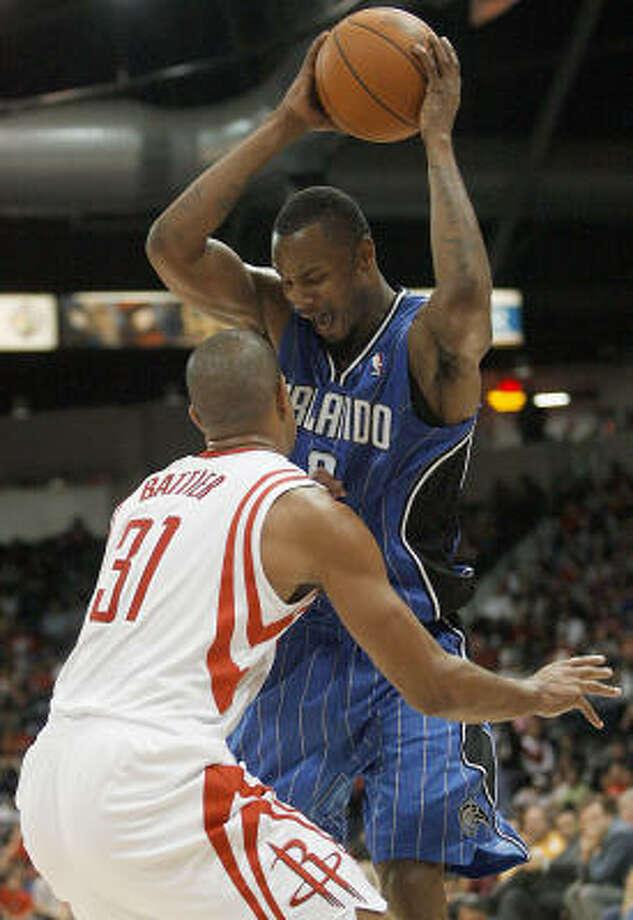 Magic forward Rashad Lewis works against Rockets forward Shane Battier during the third quarter. Photo: Delcia Lopez, AP