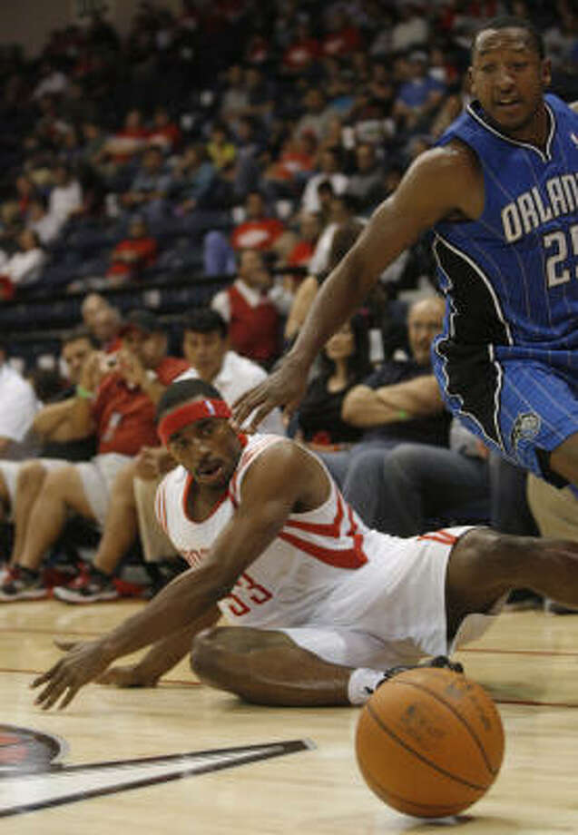 Magic guard Chris Duhon, right, and Rockets forward Mike Harris dive for a loose ball during the fourth quarter. Photo: DELCIA LOPEZ, AP