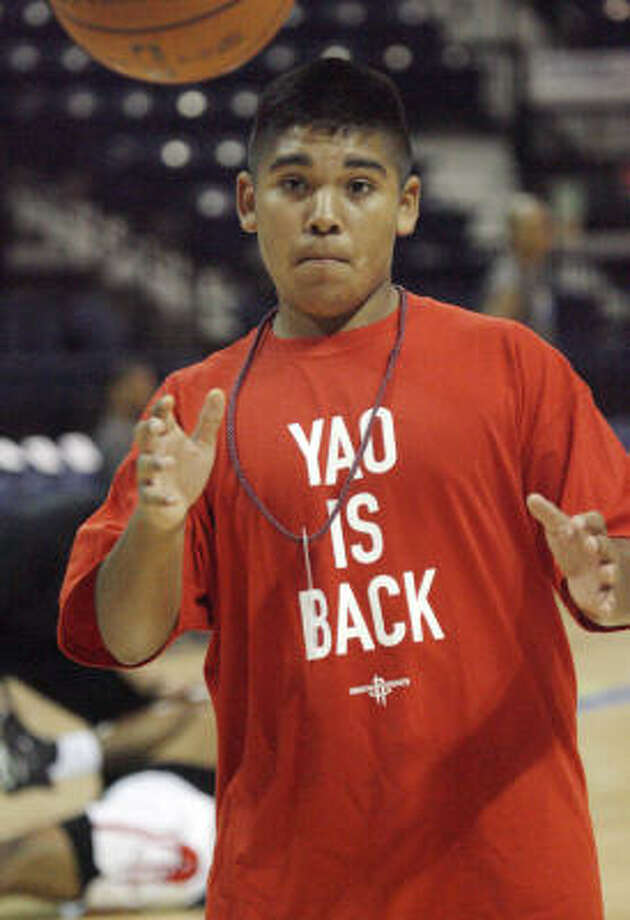 Rockets ball boy Malik Pena, 15, of Pharr, Texas, wears a Yao Is Back T-shirt during the Rockets' shootaround before the game. Photo: Delcia Lopez, AP