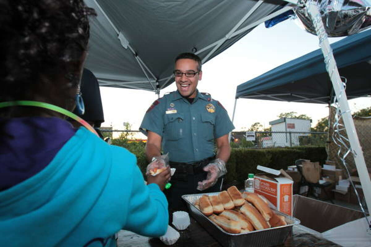 Harris County Deputy Constable Bryan Salinas serves hotdogs to northwest Houston residents.