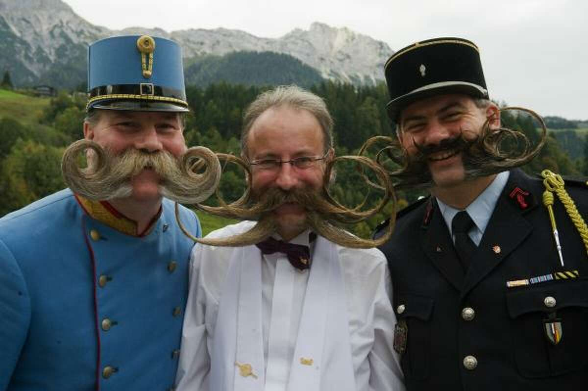 Three wide-mustached guys pose for a picture.