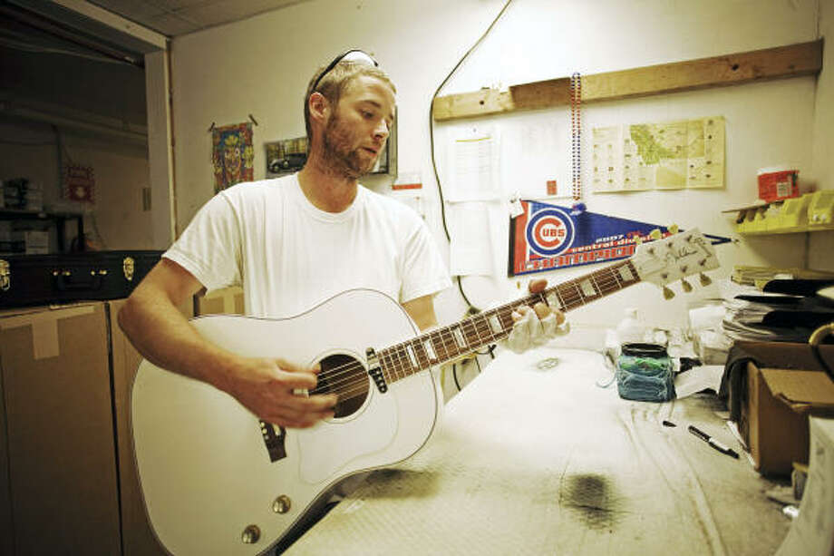 "Gibson Acoustic employee Patrick Hanson inspects one of the 70 all-white ""Imagine"" model John Lennon edition guitar, a project to honor what would have been John Lennon's 70th birthday. Photo: Nick Wolcott, AP"